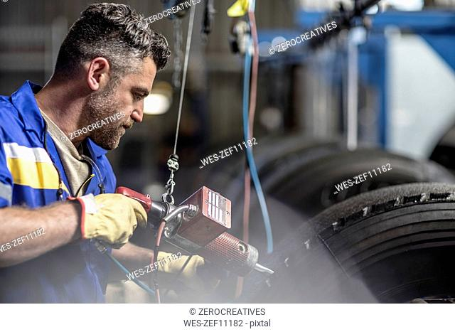 Repairman working on tire in factory