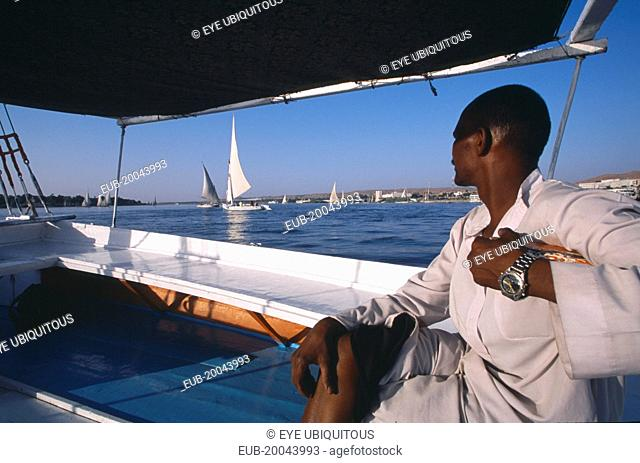 Cropped view of man on board felucca looking across water towards others