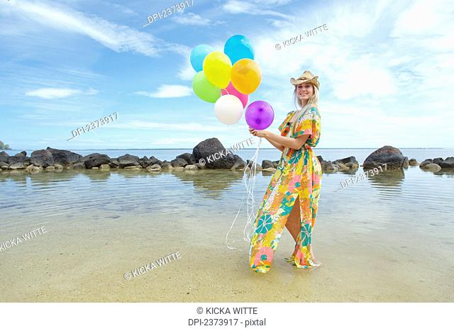 A young woman in a floral dress standing on the beach holding a bundle of colourful balloons; Kauai, Hawaii, United States of America