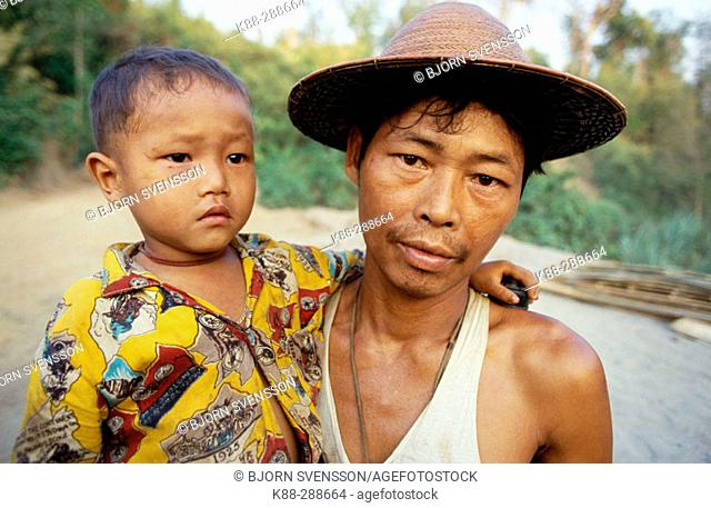 Father and son fleeing as the government troops advances. Kawthoolei (Karen State). East Myanmar