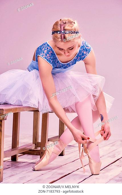 Professional ballerina putting on her ballet shoes