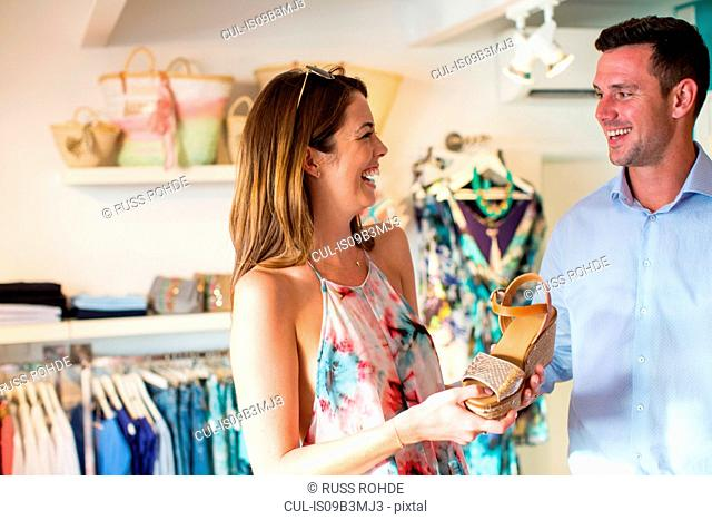 Young woman tempting boyfriend to buy sandals in boutique, Majorca, Spain