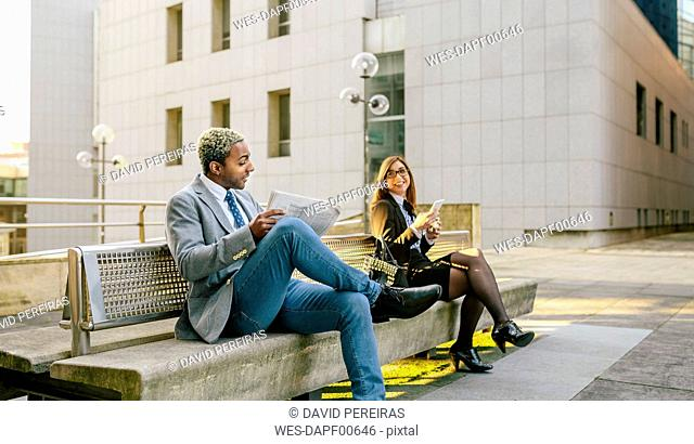 Young businessman and woman sitting on bench, talking