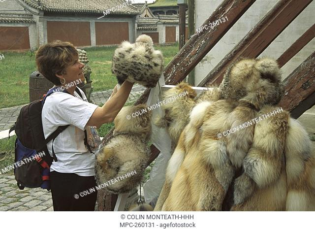 Tourist inspecting fur hats for sale made from Snow Leopard Uncia uncia, and fox fur, Ulan Baatar, Mongolia