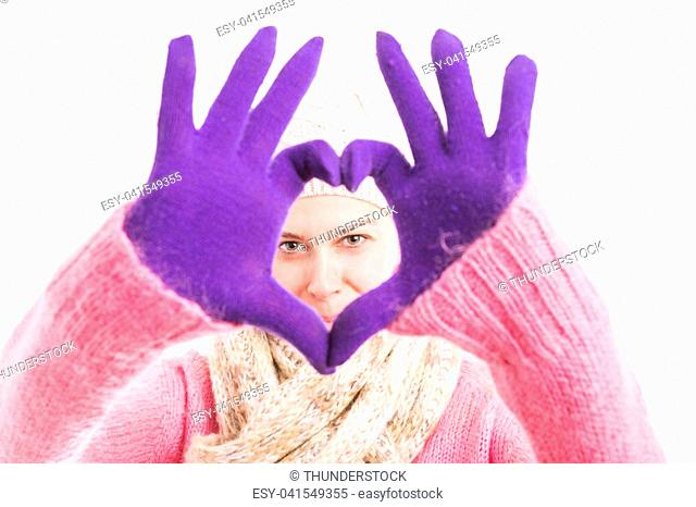 Woman wearing winter knitted clothes and gloves showing hearth shape with both hands and fingers
