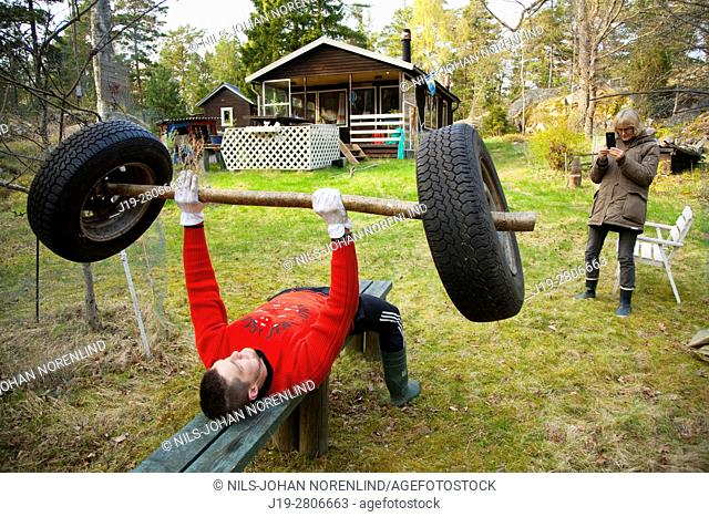 Man benchpressing in nature with homemade barbell, swedish archipelago