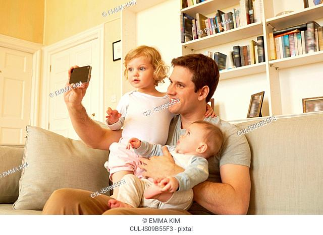 Mid adult man taking smartphone selfie with toddler and baby daughter on sofa