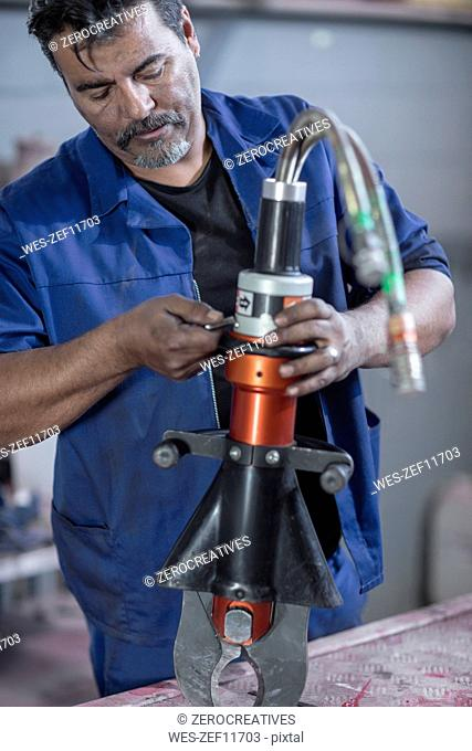 Mechanic working at fire brigade workshop, repairing claw