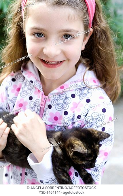 Portrait of a blond little girl with black cat
