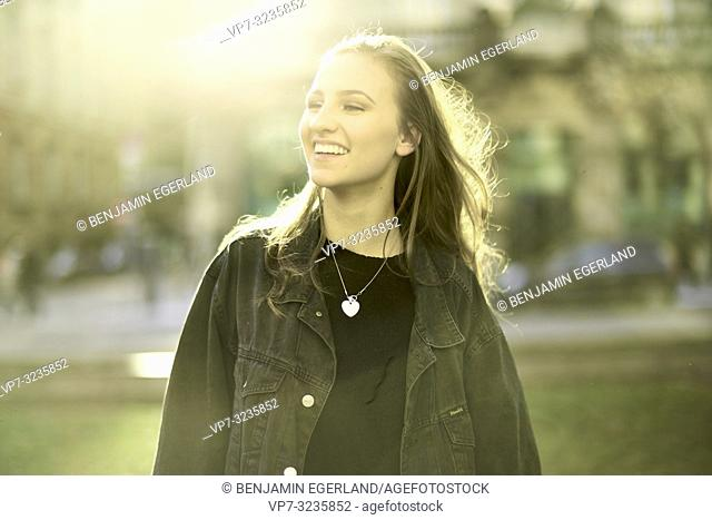 happy woman in sunlight in city, sunny weather, in Munich, Germany