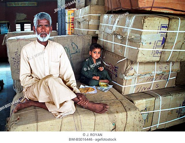 Indian man with boy sitting on packages, India, Delhi, New-Delhi