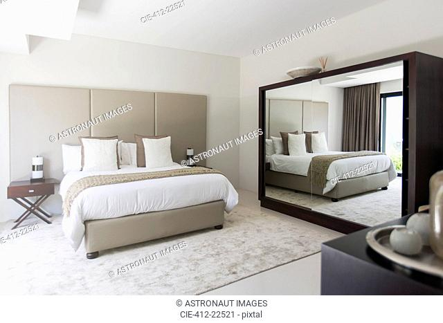 White and beige modern bedroom with double bed mirror