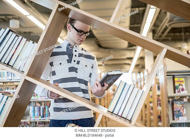 Caucasian teenage boy reading book in library
