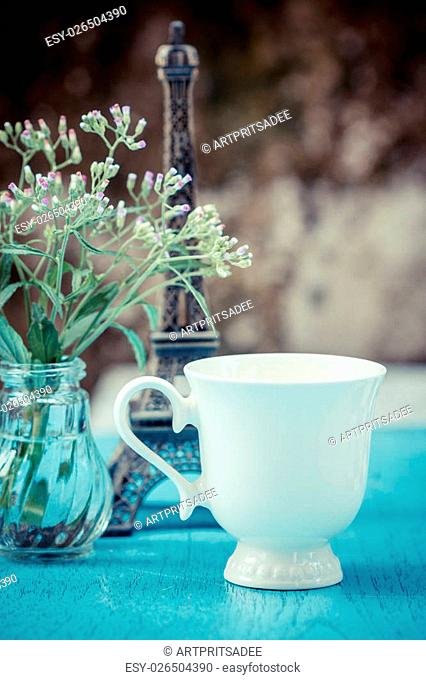 Image of morning tea cup decorated with small eiffel tower and fresh grass flower. vintage style