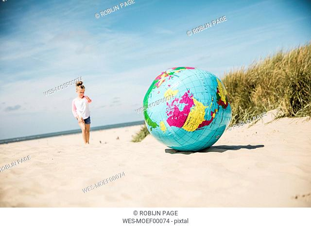 Globe on the beach with girl in background