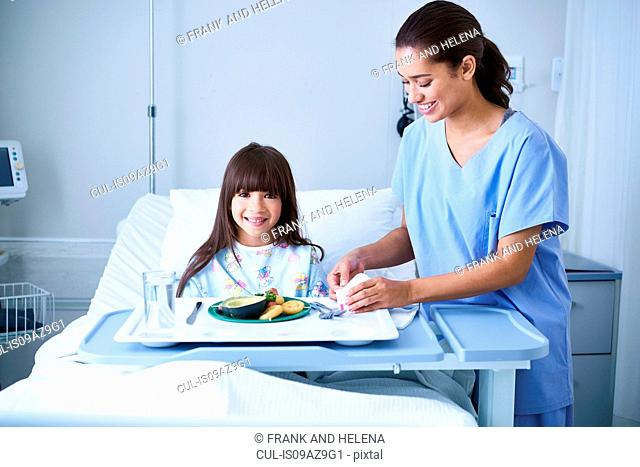 Female nurse serving lunch to girl patient with arm plaster cast in hospital children's ward