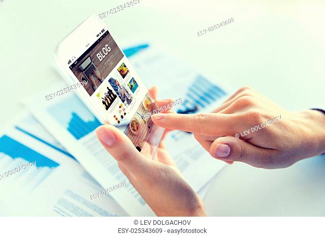 business, technology, media, internet and people concept - close up of woman hand holding and showing transparent smartphone with blog web page on screen at...