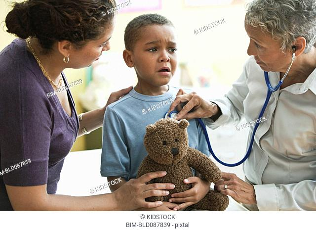 Doctor listening to anxious boy's breathing