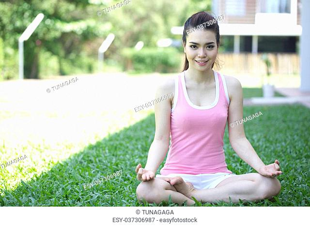 Asian woman in yoga position shot outdoor during summer