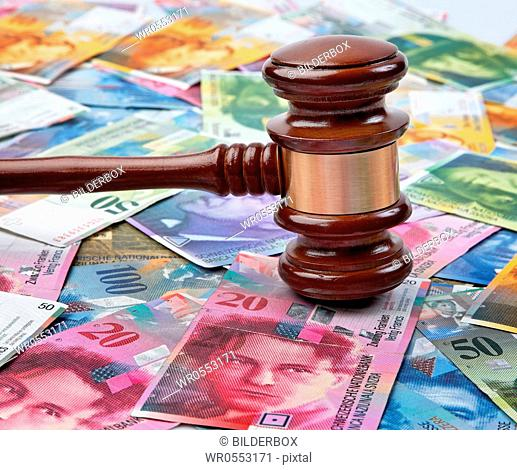 Money Swiss francs and a gavel.Legal costs in Switzerland