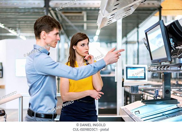 Two colleagues in industrial building, having discussion, looking at computer screen