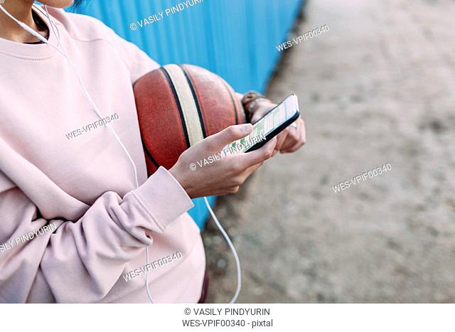 Close-up of woman with basketball, smartphone and earphones