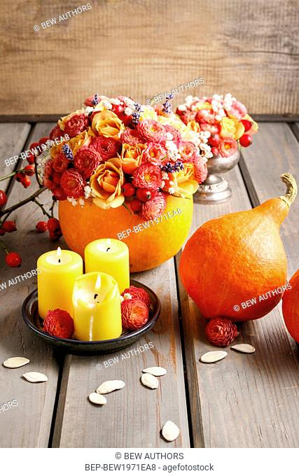 Autumn table decoration: bouquet in pumpkin and candles. Party decor