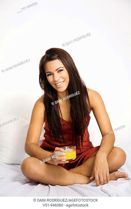 Brunette woman having an orange juice in bed