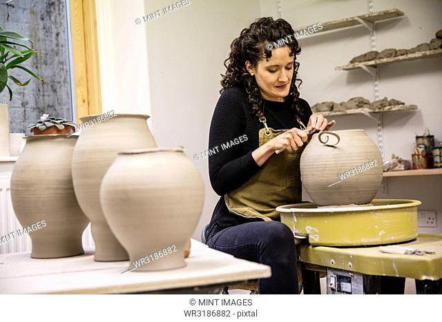 Woman with curly brown hair wearing apron working on spherical clay vase on pottery wheel