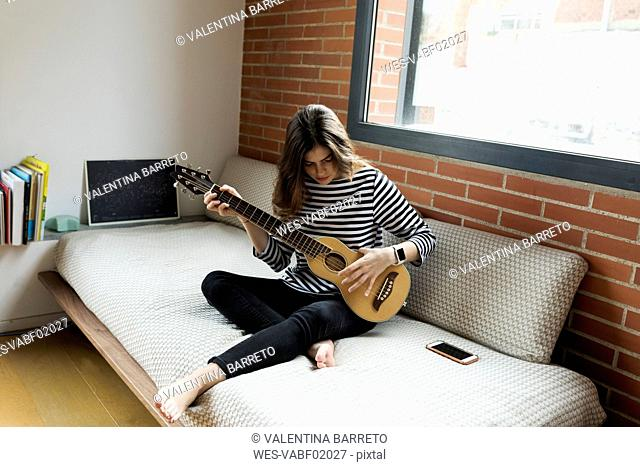 Young woman sitting on couch at home playing guitar