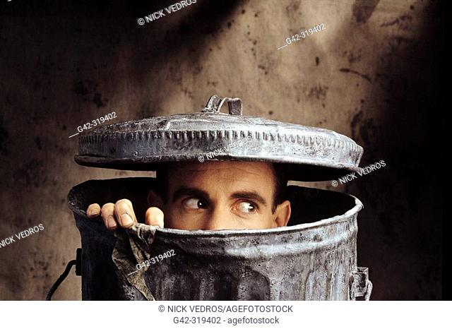 Man peering out of trash can
