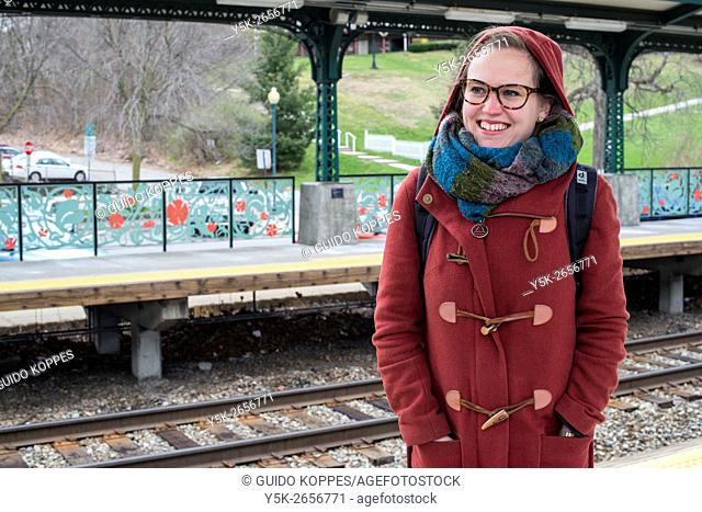 Peekskill, New York, USA. Young, female commuter waiting on a railway station's platform for her connecting train to New York City