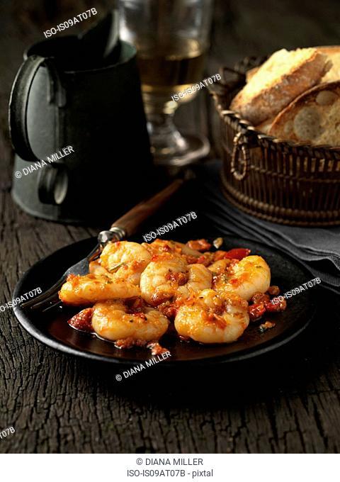 Still life starter of king prawn fra diavolo on black plate