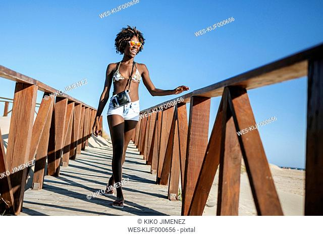 Young woman walking on boardwalk on the beach