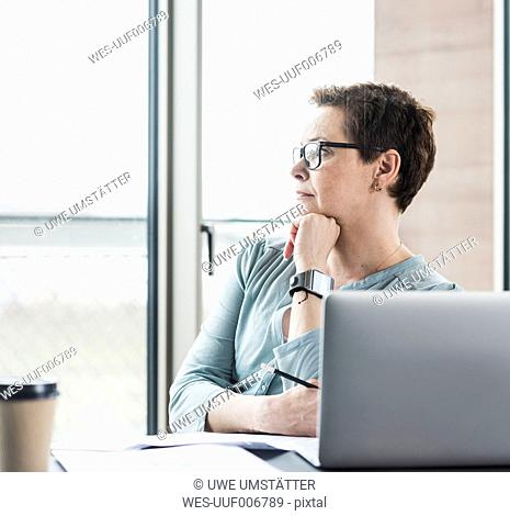 Businesswoman at desk in office thinking