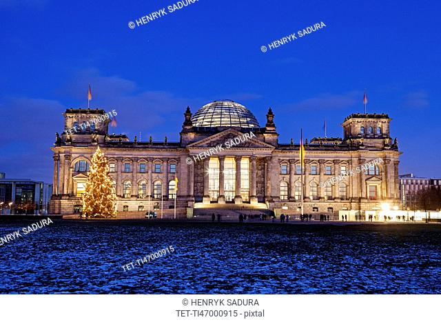 Illuminated Bundestag building and snowy lawn