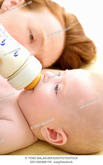 Mother feeding giving a milk bottle to her sweet baby