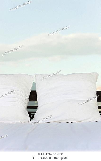 Pillows on bed, clouds in background