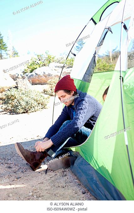 Young man sitting in tent, putting on boots