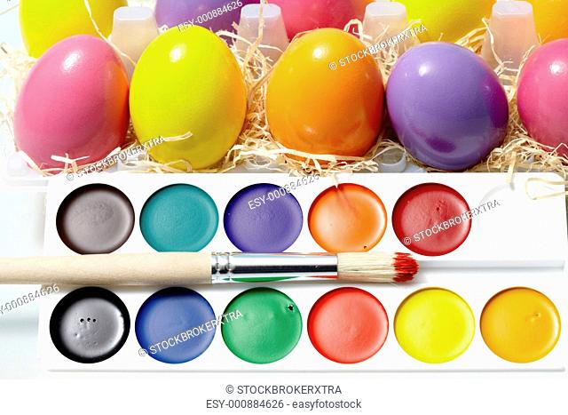 Close-up of watercolors with painting brush and Easter eggs near by