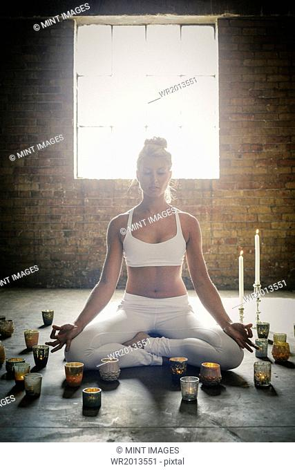 A blonde woman sitting on the floor on a yoga mat, circled by lit candles