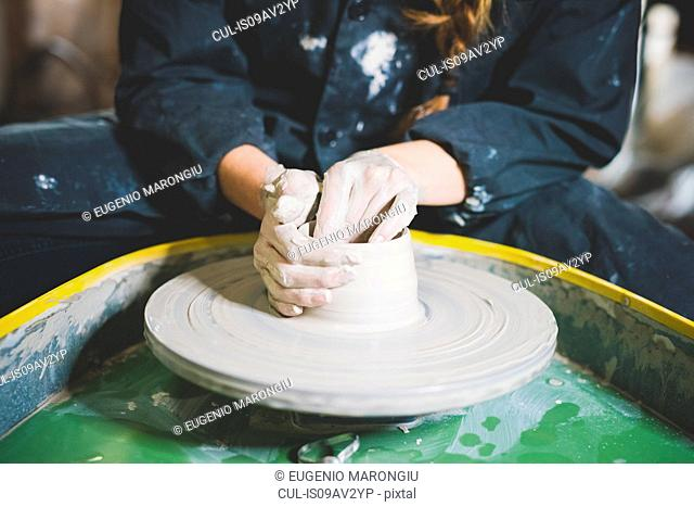 Cropped view of young woman sitting at pottery wheel making clay pot