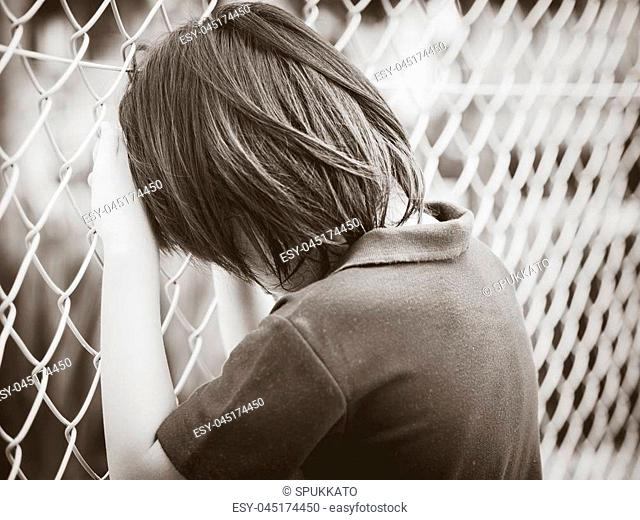 Black and white of handsome sad boy holding fence mesh netting. Emotions concept - sadness, sorrow, melancholy. Fashion & beauty concept