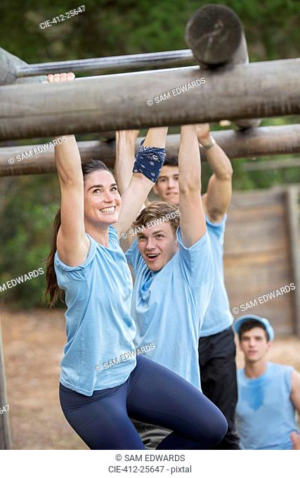 Smiling woman crossing monkey bars on boot camp obstacle course