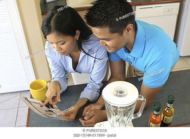 High angle view of young couple choosing color from a color swatch