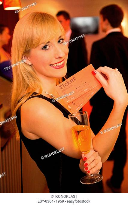 Beautiful woman presenting tickets or admission passes for a theatre, concert or cinema