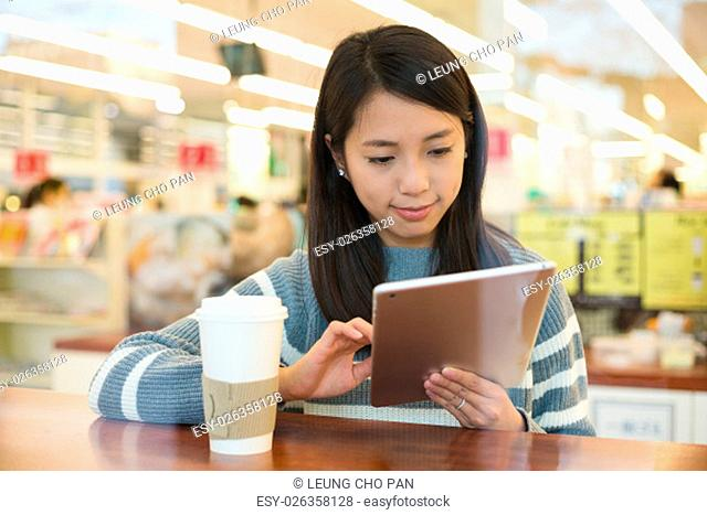 Asian young woman use of tablet pc with cup of coffee in cafe