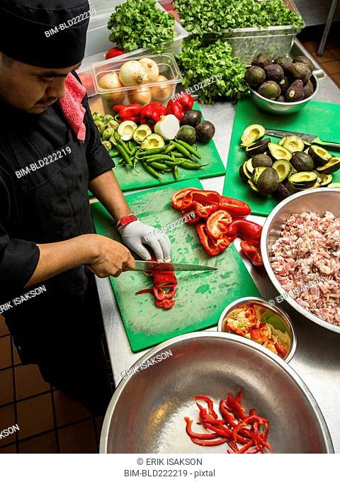 Hispanic chef cutting vegetables in kitchen