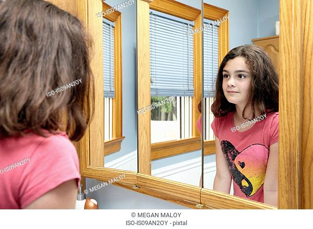 Girl staring in bathroom mirror