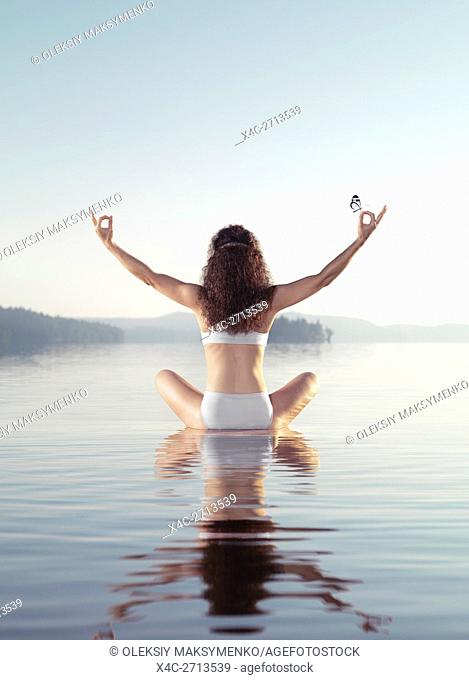 Artistic concept of a woman meditating with a butterfly on her hand. Practicing meditation on a floating platform in calm water of a lake in early morning...